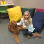 girl with golden retriever reading book